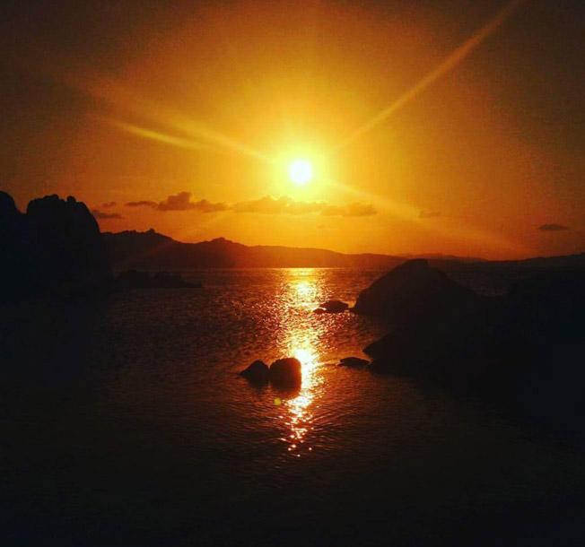 sunset at la maddalena island sardinia seen from a boat by emerald cruises